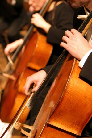 A man in a black suit playing his cello next to a woman playing her cello as they perform in a group together.