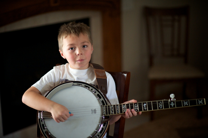 A young boy sits down in his living room and plays his banjo.