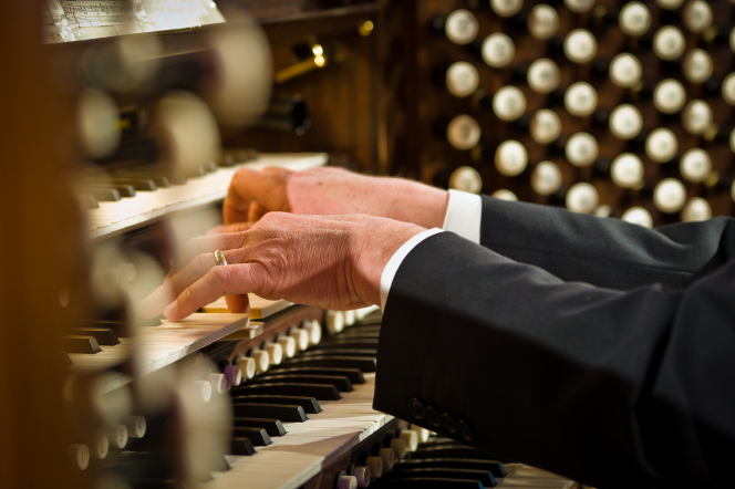 The hands of an organist are shown playing the organ at the Salt Lake Tabernacle.