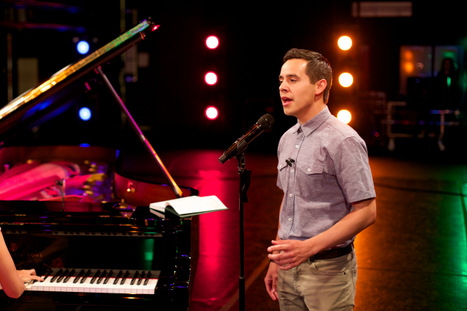 David Archuleta stands on a lighted stage and sings next to a piano.