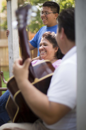 A young man is seen playing a guitar while his mother and brother stand nearby, singing.