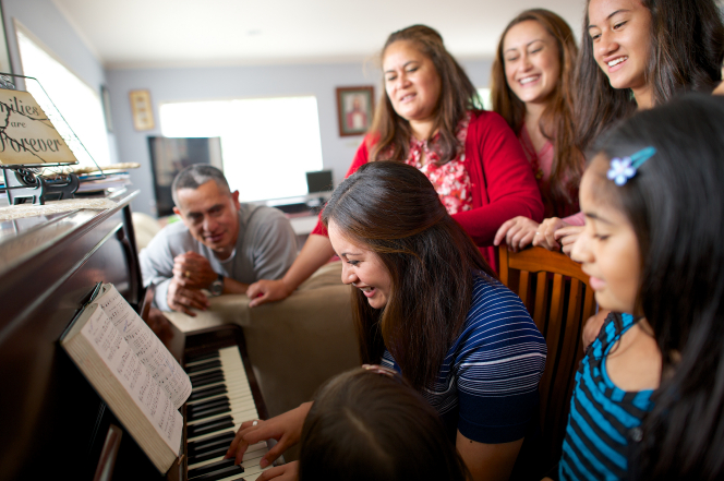 A young woman sits on a wooden chair, playing the piano as her sisters and father gather around singing.