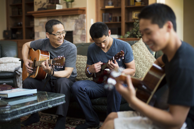 A father sits on a couch and plays a guitar beside his two sons, who are playing a ukulele and guitar.