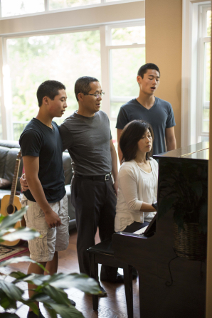 A mother plays the piano in the living room with her husband and two teenage sons standing behind her, singing along.