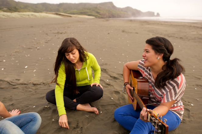 A group of young women sit together on the beach while one plays the guitar.