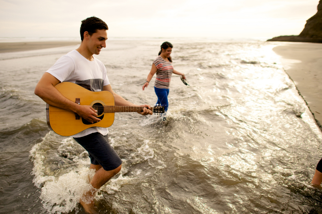 A young man walks in the water along the shore with a young woman while he plays his guitar.