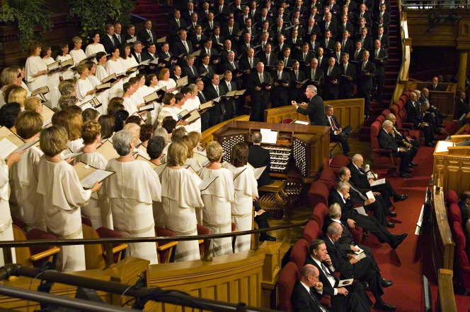 Women in white dresses and men in black suits sing in the Mormon Tabernacle Choir at the Tabernacle.