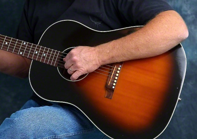 A close-up image of a man in a black shirt and jeans sitting down and strumming the strings on a guitar.