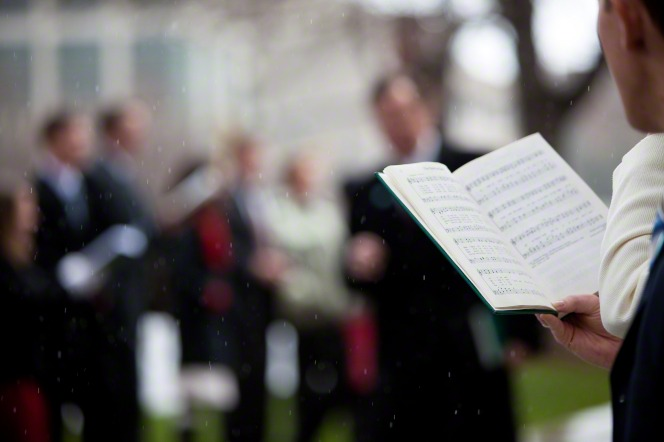 A close-up image of a man standing and holding a hymnbook while caroling with others in the snow.