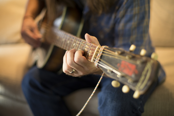 The hands of a young man are seen strumming a guitar while he sits on a couch.