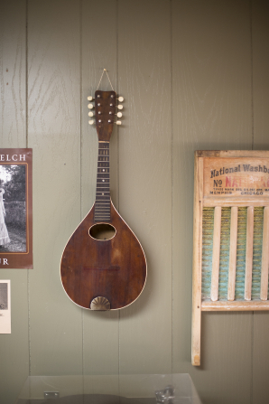 A mandolin hangs on a gray wall next to an old washboard and poster.