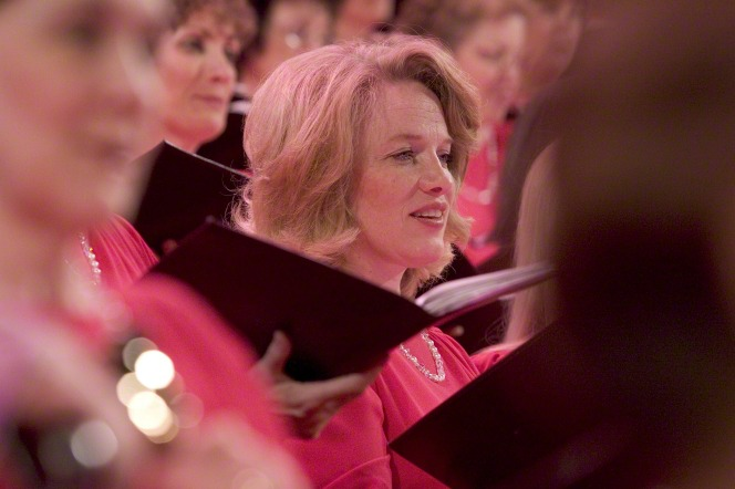 A woman with blond hair and a red dress, holding sheet music while standing and singing in the Mormon Tabernacle Choir.