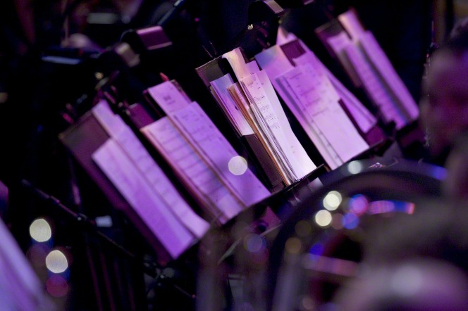 Light shining down on sheet music stands lined up with sheet music ready for musicians to read from.