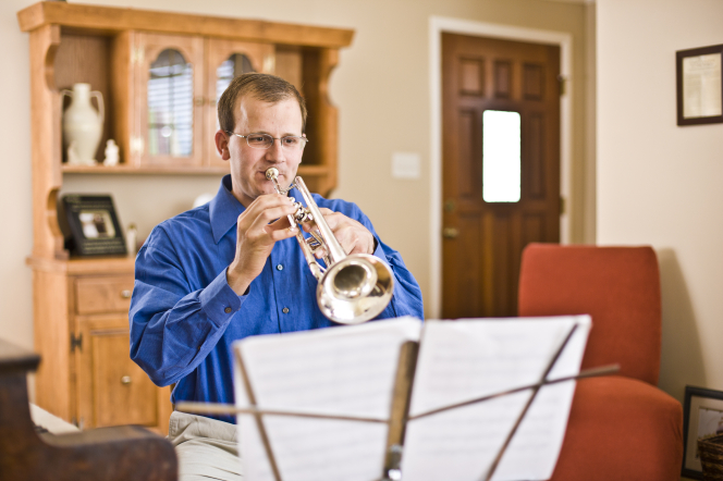 A man with glasses sits on a bench in the living room and plays his trumpet with music on a stand in front of him.