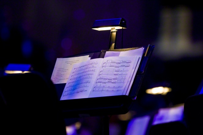 A lamp shining down on a music stand with sheet music for a performer to read from.