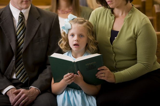 A young girl with a bow in her hair and a light blue dress sits between her parents while singing from a hymnbook.