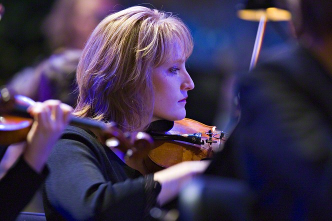 A woman with blond hair and a black blouse performs on a violin with other violinists in a concert.