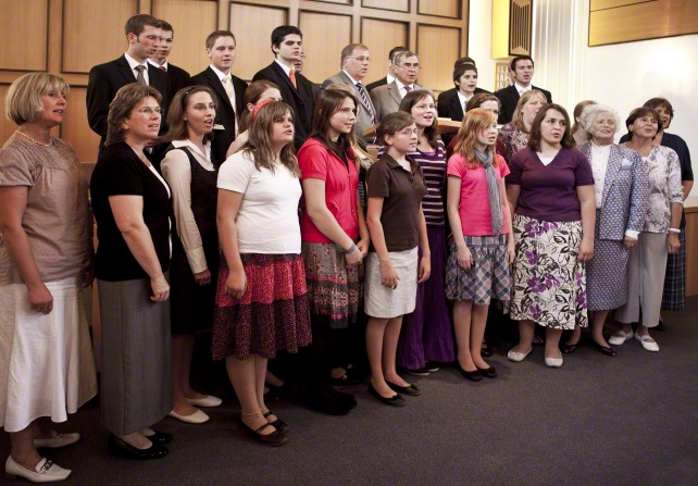 A ward choir consisting of adults and youth singing, with the men standing behind the women.