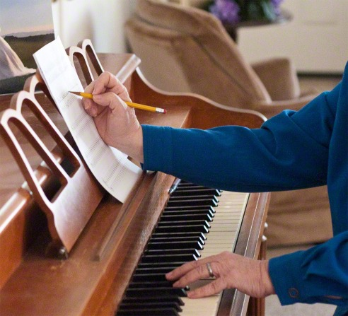 A woman sits at a piano and touches the keys with one hand and makes notes on her sheet of music with the other.