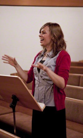 A young woman singing and standing behind a music stand while conducting a choir in song.