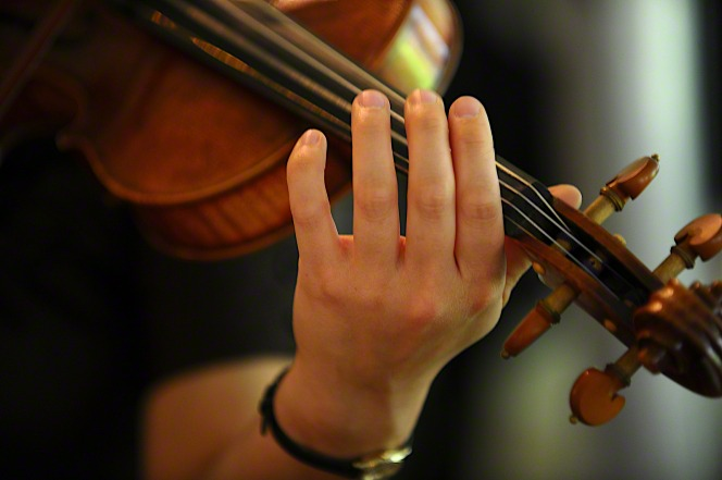 A close-up image of a woman's hand playing on a violin.