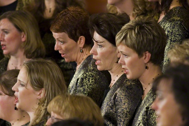 A group of women in black and gold outfits standing in rows and singing in a choir.