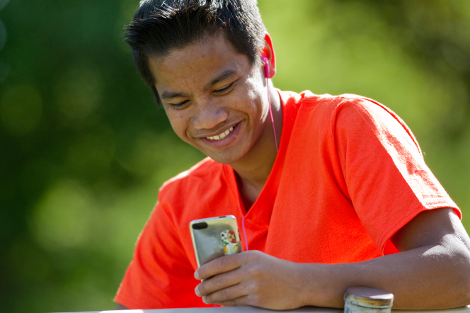 A young man wearing headphones and a bright red shirt sits down outside and chooses music to listen to on his iPod.