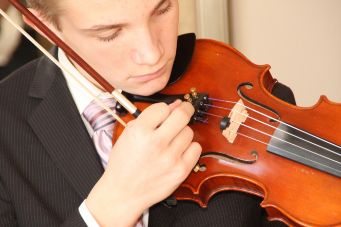 A young man in a suit tuning his violin.