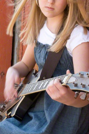 A young woman with blond hair and a blue dress playing a guitar outside.