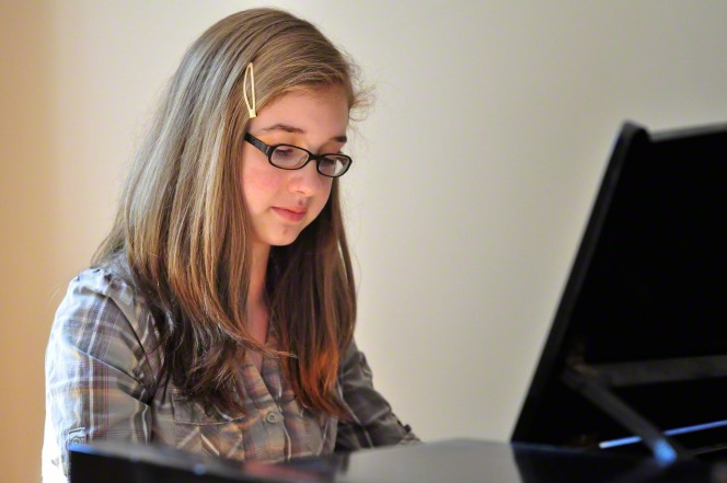 A young woman with brown hair and glasses looking down at the keys while playing the piano.