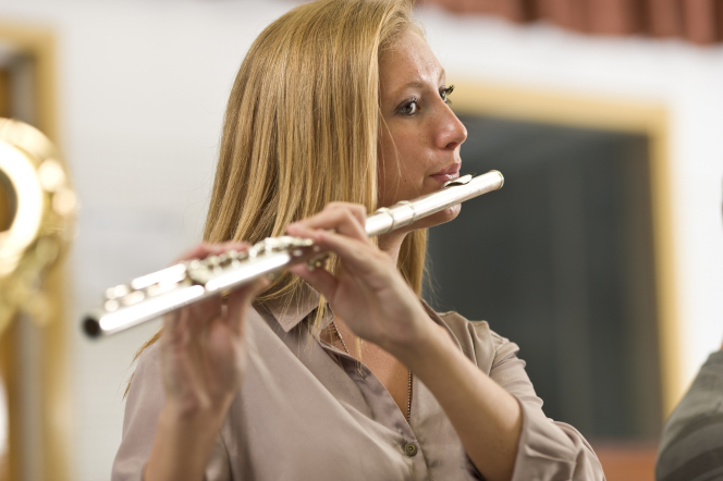 A young woman with long blond hair stands and plays the flute with people on either side of her playing as well.