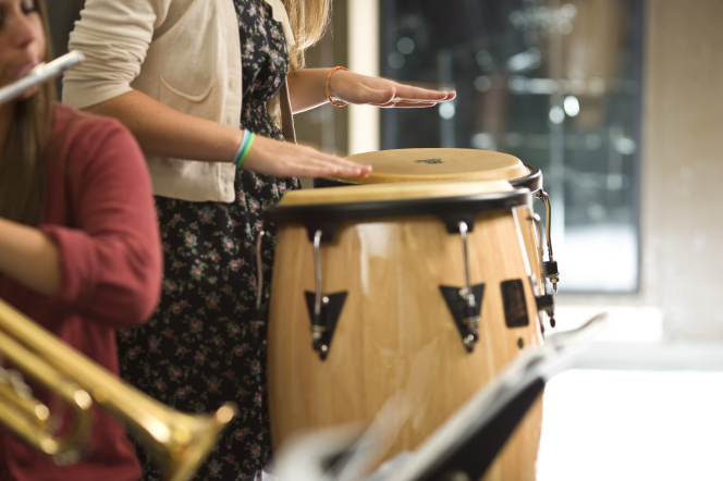 The hands of a young woman are seen playing two drums.