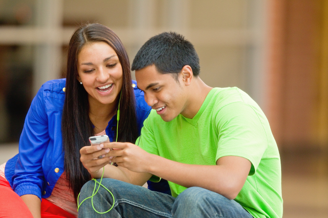 A young woman and young man share a set of headphones to listen to music from an iPod together while sitting down outside.