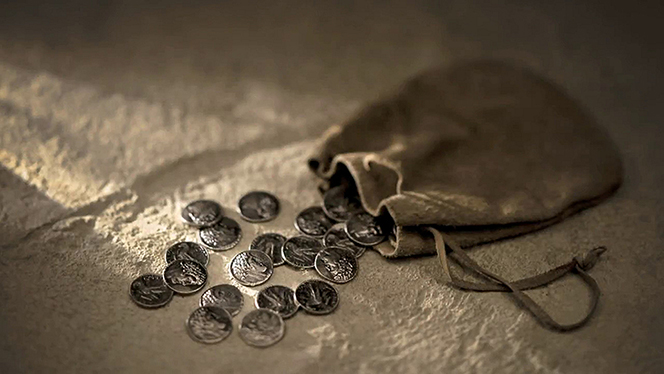 A small leather bag spilling small silver coins over a stone surface.