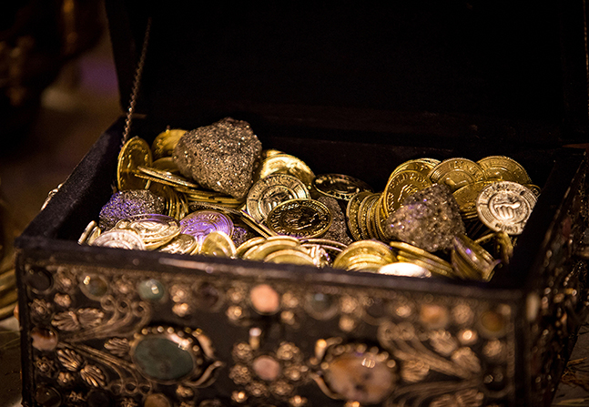 A small, ornate wooden chest filled with replicas of gold coins.
