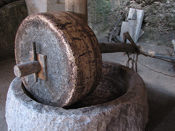 A large gray stone fashioned into a wheel to act as a millstone.