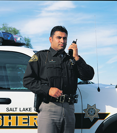 "A man in a police uniform talking into a police radio and standing next to a vehicle marked ""Sheriff."""