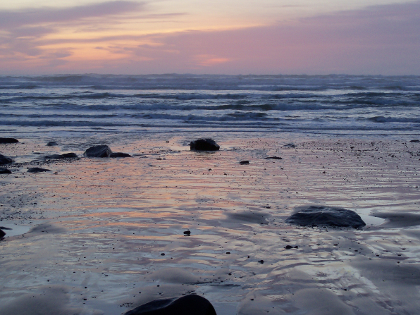 Rocks on the shore and waves in the distance at sunset.