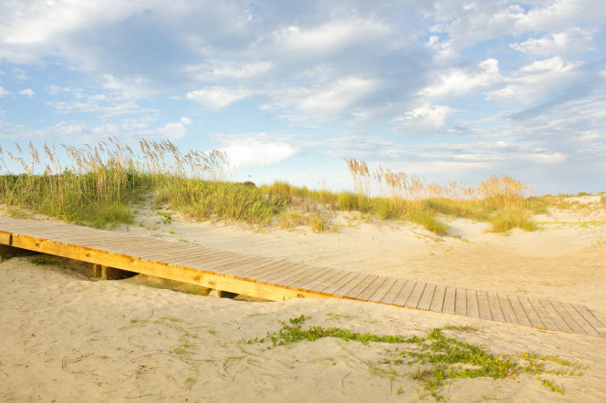 A wooden boardwalk leading through the sand and brush, with clouds in the sky.