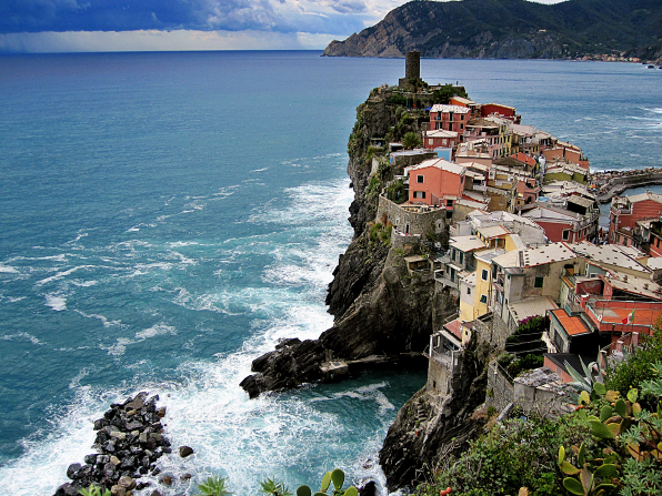 A small village on a cliff against the sea in Italy with storm clouds in the distance.