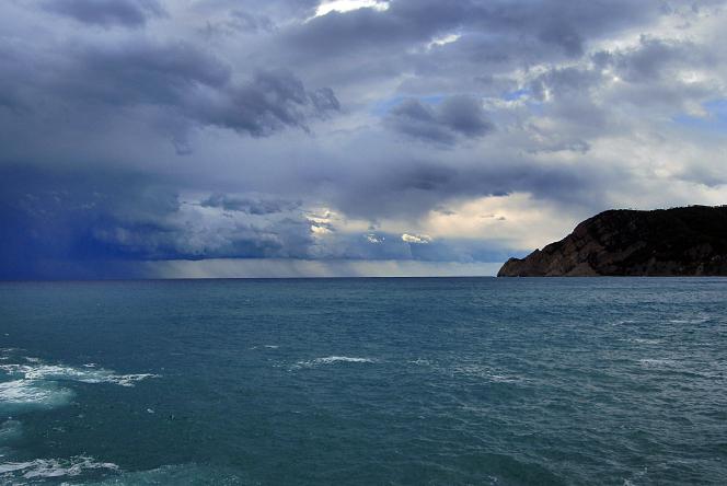 A dark, cloudy sky over the ocean and a rocky coast.