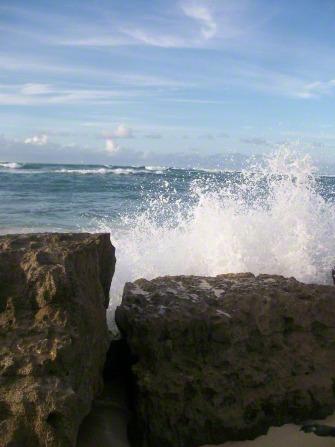 Waves crash on two cylindrical rocks in Hawaii.