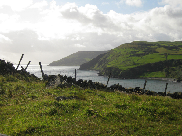 Ireland coastline with green cliffs, rocks, and fence along the ocean water.