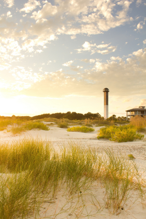 The sun shining down on a lighthouse surrounded by sand and green brush in South Carolina.