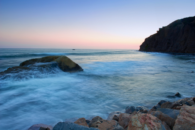 The Pacific Ocean bordered by rocks on the California coastline at dusk.