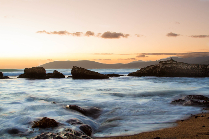 A sunset over distant mountains and a rocky coastline.