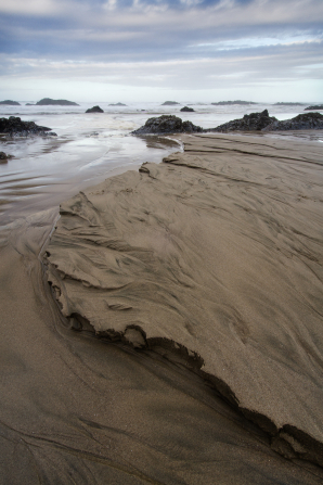 Large rocks rising through the ocean water near sand on the Oregon coast.