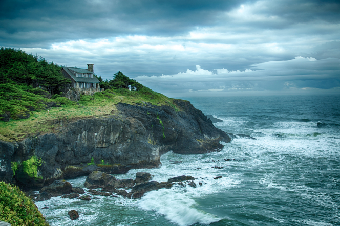A house surrounded by trees on a rocky cliff and coastline.