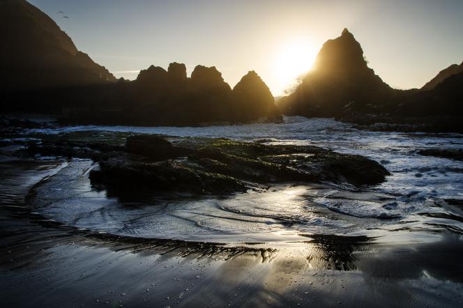 The sun sets behind tall rocks on an Oregon beach.