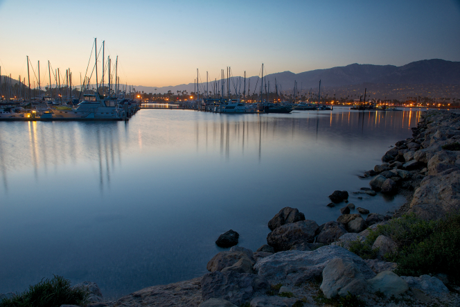 Sailboats at dusk in the Santa Barbara marina bordered by rocks.